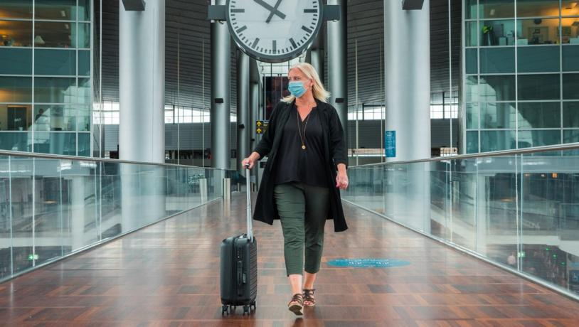 A woman walks through Copenhagen airport in a face mask during the coronavirus period