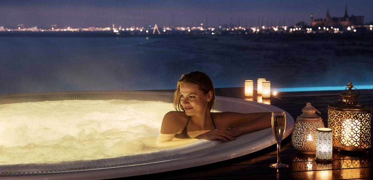 Woman sitting in a hot tub overlooking the sea at Marienlyst Beach Hotel in North Zealand, Denmark