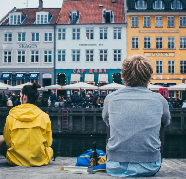 People sitting by the dock in Nyhavn, Copenhagen